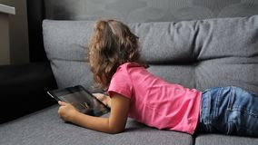 Baby girl lying on sofa with tablet. Little girl lying playing on tablet stock footage
