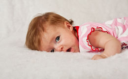 Baby girl lying on soft fluffy surface Royalty Free Stock Photography