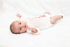Baby girl lying on white. Funny baby girl lying on white background royalty free stock photo