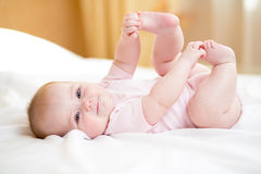 Baby girl lying on white sheet and holding legs Stock Photos