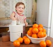 Baby girl making fresh orange juice Stock Images