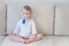 Baby girl making inhalation with mask on her face Stock Photography