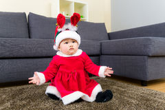 Baby girl with x mas dressing and sitting on carpet Stock Photos