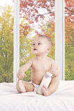 Baby girl with milk bottle on bedroom Stock Image
