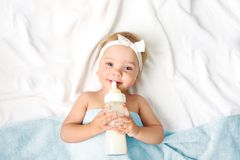 Baby girl with milk bottle empty space background. royalty free stock image