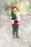 Baby Girl In Mittens Holding Small Christmas Tree with Snow Effe Stock Photos