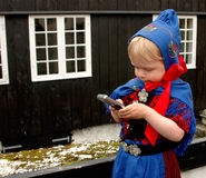 Baby girl with mobile phone. Baby girl (2 y.o.) in Faroese national costume using a mobile phone during St. Olaf's Days (the national holidays Royalty Free Stock Image