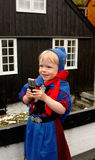 Baby girl with mobile phone. Baby girl (2 y.o.) in Faroese national costume using a mobile phone during St. Olaf's Days (the national holidays Royalty Free Stock Images