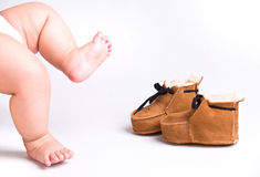 A baby girl and moccasins Stock Images
