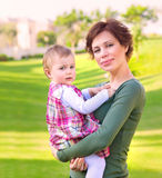 Baby girl with mom in the park. Portrait of beautiful young mother carry little baby girl in spring park, spending time outdoors, happy loving family concept Stock Image