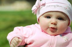 Baby Girl in Mommy Loves Me Hat. Beautiful Baby Girl in Pink Mommy Loves me Hat with Bow and Pink Sweatshirt in the Park Royalty Free Stock Photos