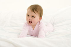 Baby girl (3-6 months) crawling, smiling Stock Photography