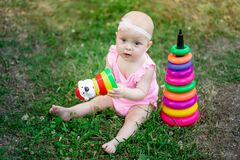Baby girl 10 months old sitting on the grass in the summer and playing pyramid, early development of children, outdoor games