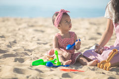 Baby girl with mother at the beach play with toys on the sand Royalty Free Stock Image