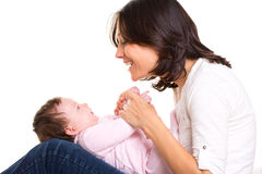 Baby girl on mother jeans knees playing together Stock Photos
