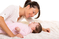 Baby girl and mother lying happy playing together Stock Image