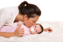 Baby girl and mother lying happy playing together Stock Images