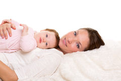 Baby girl and mother lying happy together on white fur Royalty Free Stock Images