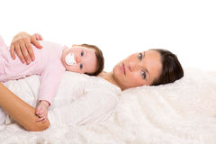 Baby girl and mother lying happy together on white fur Stock Photography