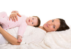 Baby girl and mother lying happy together on white fur Royalty Free Stock Photo