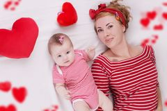 Baby girl and mother lying among plush hearts Stock Images