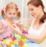 Baby girl with mother paint Easter eggs Stock Photos