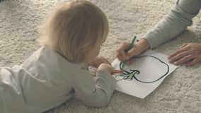 Baby girl with mother paints picture with pencils stock footage
