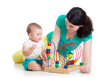 Baby girl and mother play with educational toy Stock Photo