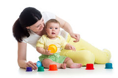 Baby girl and mother play together with cup toys Royalty Free Stock Photos
