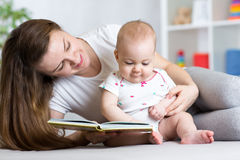 Baby girl and mother reading a book indoor Royalty Free Stock Images
