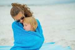 Baby girl with mother wrapped in towel Stock Image