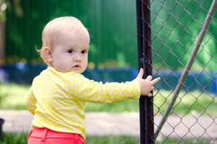 Baby girl near the fence. Little girl looks back while standing near the fence stock photography