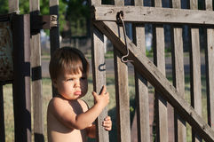 Baby girl near fence outdoor at summer with bronze tan Royalty Free Stock Photos