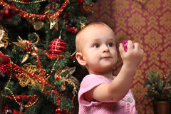 Baby girl next to a Christmas tree Royalty Free Stock Images