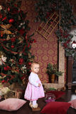 Baby girl next to a Christmas tree Stock Image