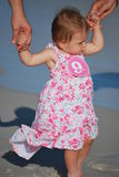 Baby girl. Nine-month girl walks nicely on the wet sand and holding hands men royalty free stock photography