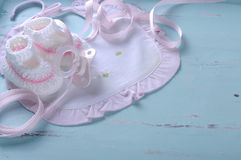 Baby girl nursery bib and booties on vintage blue background Royalty Free Stock Images
