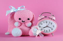 Baby girl nursery cute bunny toy, dummy pacifier and clock Royalty Free Stock Photos