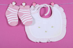 Baby girl nursery cute pink and white stripe socks and bib. Hanging from pegs on a line against a pink background for baby shower or newborn girl greeting card stock images