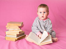 Baby girl with old books reading on pink background. Forwardness Stock Photos