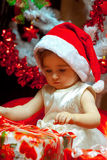 Baby girl opens her first Christmas gift Royalty Free Stock Images