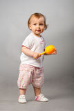 Baby girl with orange maraca. Royalty Free Stock Photos