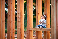 Baby girl outdoor with wood bench Stock Image
