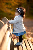Baby girl outdoor with wood bench Stock Photo
