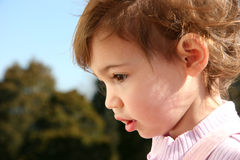 Baby Girl Outdoors. Profile of beautiful baby girl outside against a tree background. Shot with Canon 20D stock images