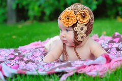 Baby girl outdoors in a brown knitted cap Royalty Free Stock Images