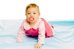 Baby girl with pacifier crawling on the blue coverlet. Studio Royalty Free Stock Images