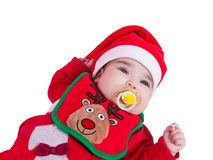 Baby girl with pacifier or dummy, red babygrow or onesie, Rudolph reindeer bib, Santa Claus hat Stock Images