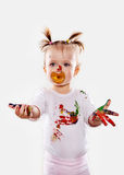 The baby girl with a pacifier in gouache soiled hands and shirt isolated Stock Photos