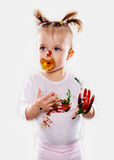 The baby girl with a pacifier in gouache soiled hands and shirt isolated Royalty Free Stock Images